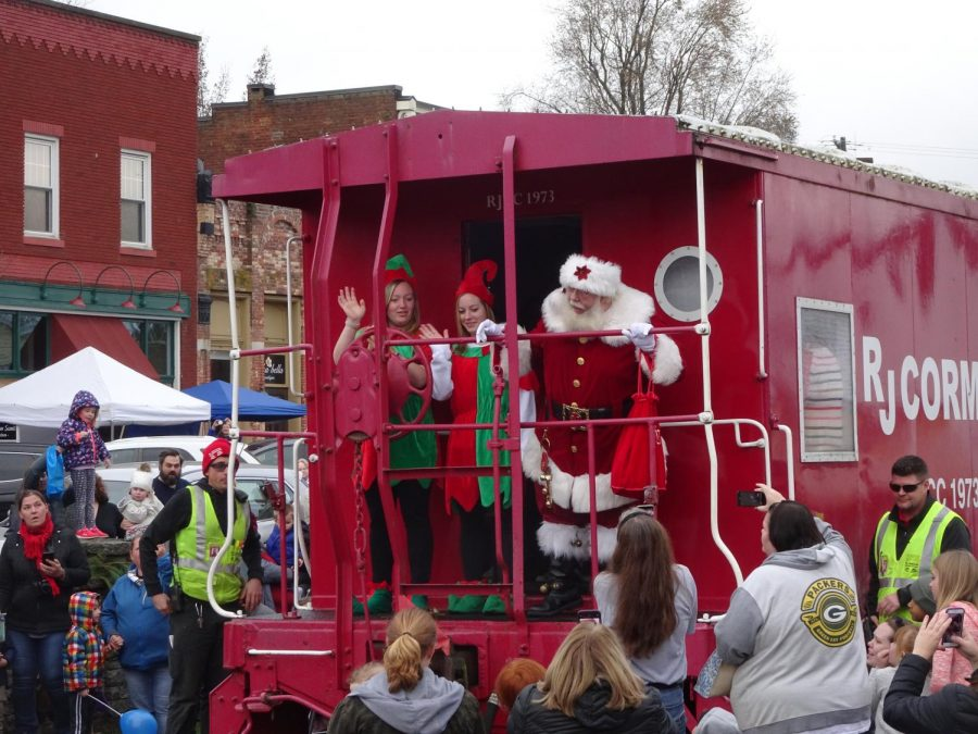 Santa Claus steps out of the train and the children clap. Photo by Arissa Keith.