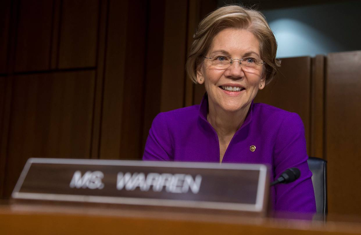 Presidential candidate Elizabeth Warren sits in front of her nameplate
