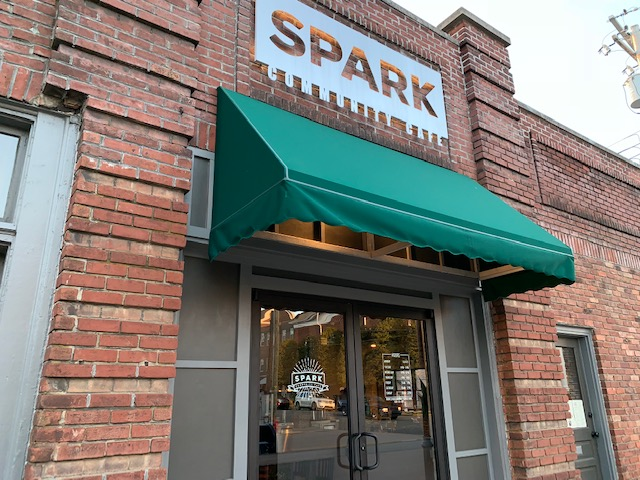 The+Spark+Community+Cafe%27s+sign+is+lit+up+for+opening+night.