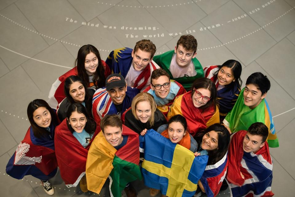 International students hold the flag of the country they study in.