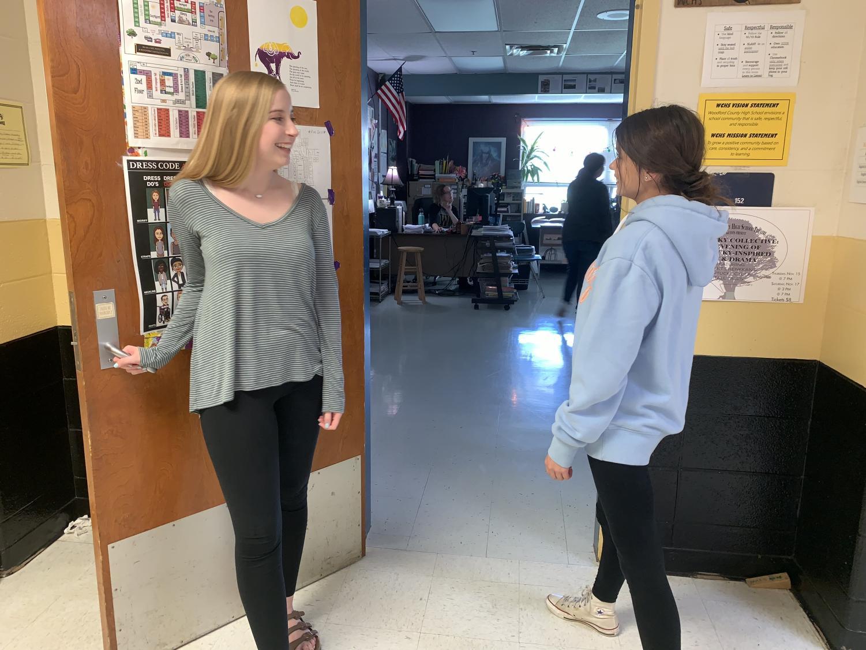 Ashlyn Martin (11) invites Anna Ward (10) into a classroom.