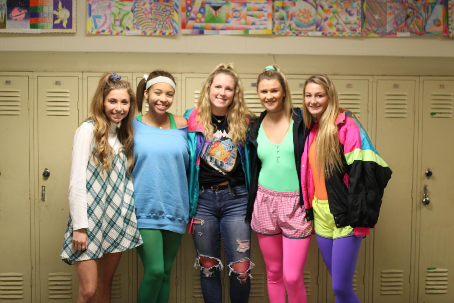 Seniors Casey Montgomery, Karigan Smith, Abbey Moffett, Kasey Abel, and Gabby Blakenship pose for a picture against the lockers in their best 80's attire.