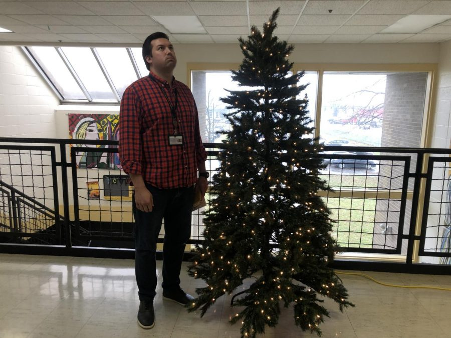 Mr.+Wilkins+stands+by+the+school%27s+Christmas+tree+ready+for+a+break.+Photo+by+Jamie+Hobbs.