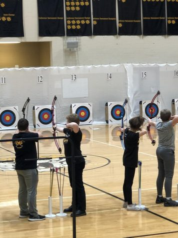 Archers line up at the 15-meter line to release their first practice shot.