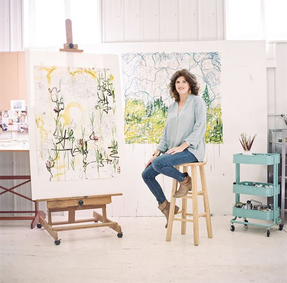 Alex K. Mason sits on a stool in her studio in by one of her in progress paintings sitting on an easel with another painting behind her called Countryside, 2015 (Abstract,  Flora, Landscape).