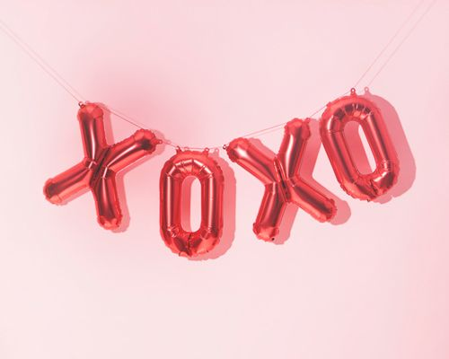A very fun and bright Valentine's Day balloon display taken in front of a soft pink background.