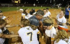 Two players dump water on head coach Les Anderson after they won regionals in 2019.