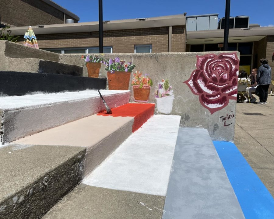 A big rose and flower pot paintings going up the wall of a colorful staircase