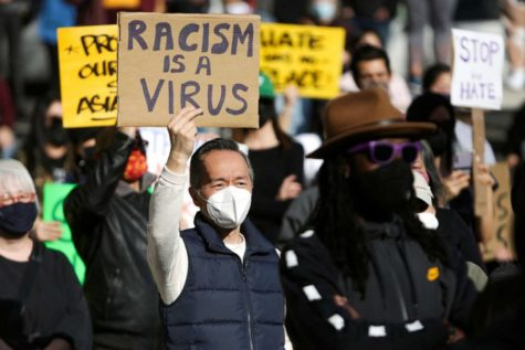 """A man holds a sign at the """"We Are Not Silent"""" rally against anti-Asian hate in Seattle, Washington. Photo by Jason Redmond, Getty Images."""