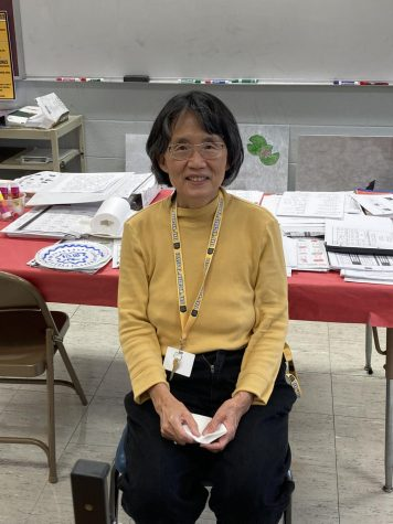 Ms. Chou sits at her desk in her classroom.