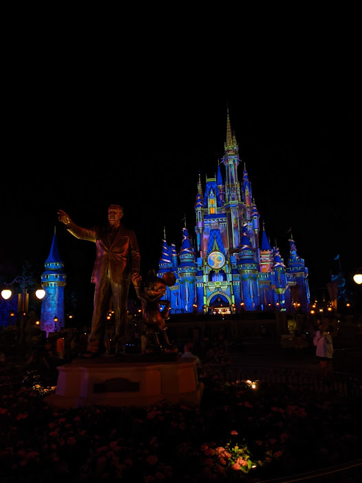 The beautiful Cinderella castle in the Magic Kingdom with Walt Disney and Mickey Mouse out front.